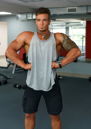 straining: At gym. Strong man posing with his muscles straining Stock Photo