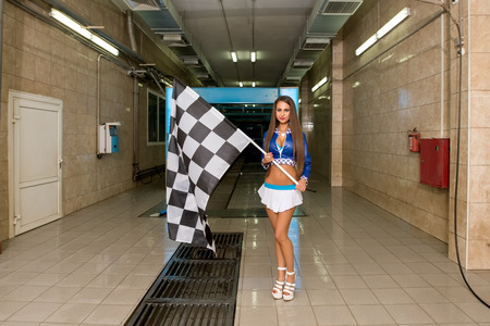 Sexy brunette posing with checkered flag at car wash