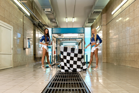 two car garage: Car wash. Charming leggy girls posing with checkered flags Stock Photo