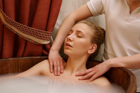 massaged: In spa. Girls shoulders massaged during she taking bath