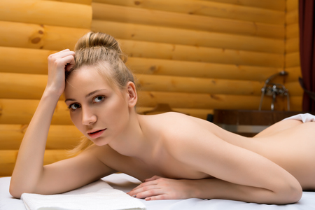 chica desnuda: Foto de la hermosa chica desnuda posando tumbado en el salón del balneario