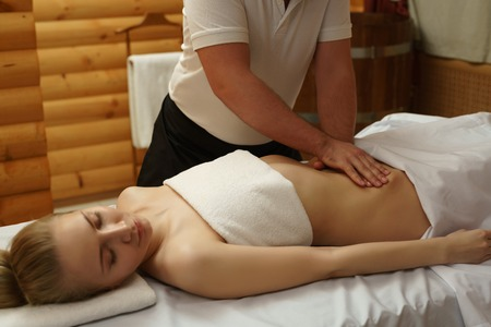In spa center. Image of masseur massaging girls belly Stock Photo