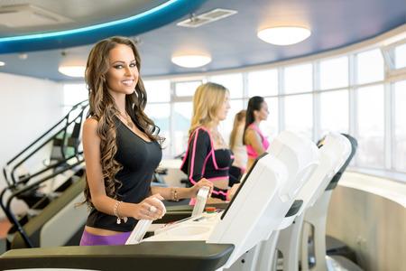 simulator: In gym. Smiling brunette posing while training on simulator