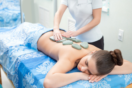 girls naked: Pretty woman getting hot stone massage in spa salon Stock Photo