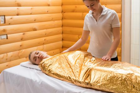 Body wraps. Photo of pretty girl relaxing in spa salon