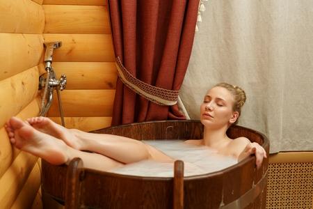 woman bath: Spa. Beautiful young woman taking bath with relaxing oils