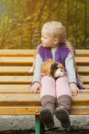 cavie: Image of lovely little girl sitting on bench with her cavy