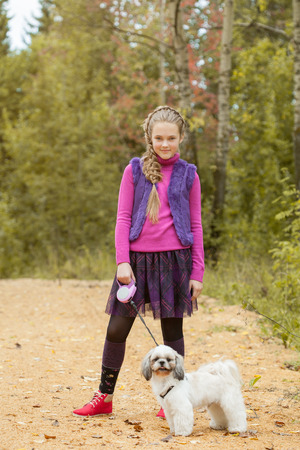 charming girl: Image of charming little girl walking with puppy in park Stock Photo