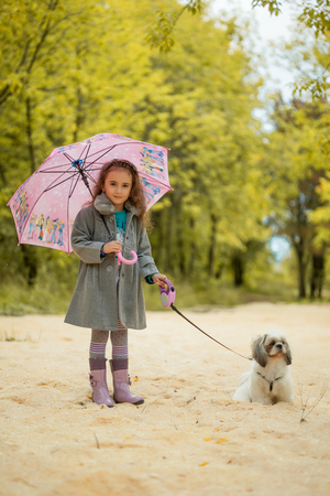 cute dogs: Image of pretty little girl walking with cute dog in park Stock Photo