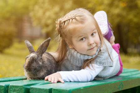 Cute brown-eyed girl lying on bench with rabbit, close-up