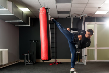healthy men: At gym. Image of handsome boxer training his kick