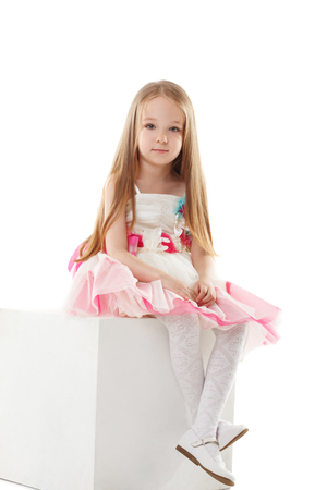 child model: Image of charming fashionista sits on cube in studio, close-up