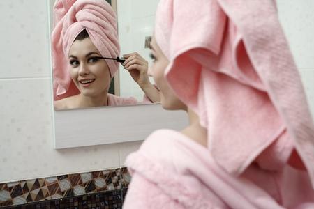 Image of smiling flirtatious woman using mascara