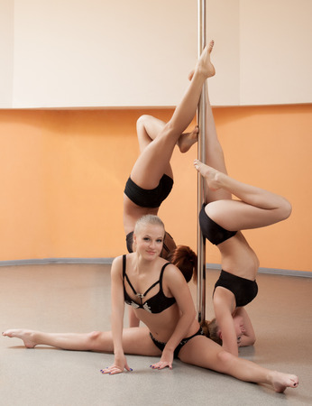 Image of cute young pole dancers posing with pylon Stock Photo