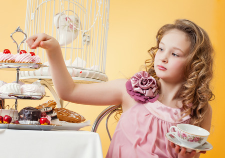 smartly: Image of smartly dressed little girl drinking tea with cake