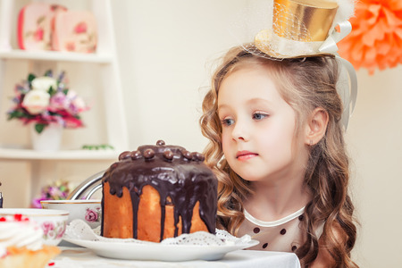 fascinating: Fascinating little girl looks thoughtfully at cake