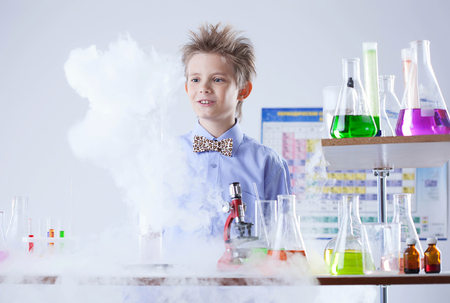 flasks: Curious pupil posing with test tubes and flasks, close-up