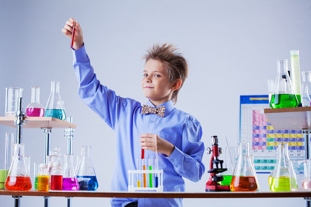 experimenter: Cute boy posing with variety of reagents in laboratory, close-up