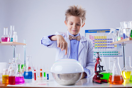 experimenter: Smiling boy conducting experiment in chemistry lab, close-up
