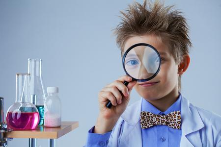 experimenter: Portrait of curious boy looking through magnifier, close-up