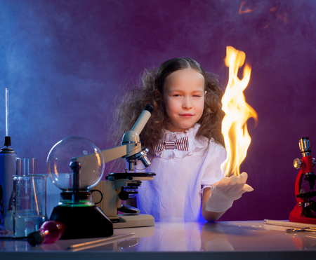 fire shows: Image of slyly smiling girl shows chemical trick - fire in palm
