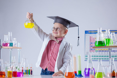 experimenter: Image of little chemist posing with variety of reactants