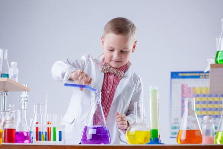 experimenter: Inquisitive naturalist mixes reagents in flask, close-up