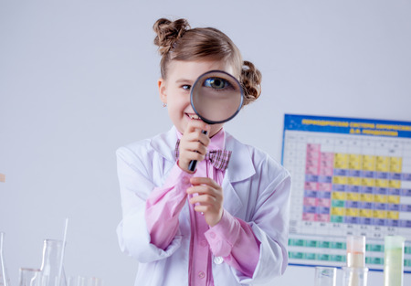 Adorable girl looking through magnifying glass, close-up photo