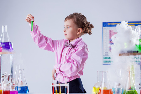 Image of stylish schoolgirl posing in chemistry lab, close-up photo