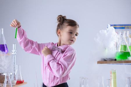Attentive schoolgirl conducting experiment in laboratory photo