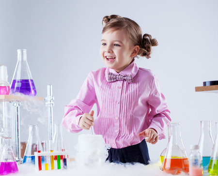 Merry girl posing with variety of flasks and test tubes photo