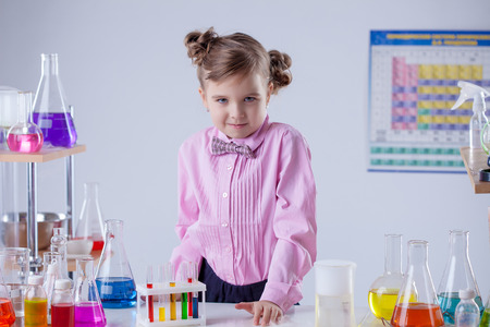 Image of serious little laboratorian looking at camera photo