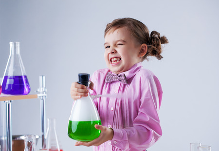 Image of cute little girl posing with heavy flask, close-up photo