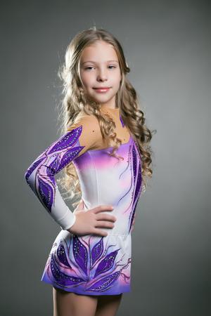 Cute artistic gymnast posing in dress for performances, on gray background