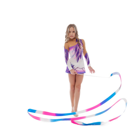 Cute athlete rhythmic gymnastics performs with ribbon, isolated on white