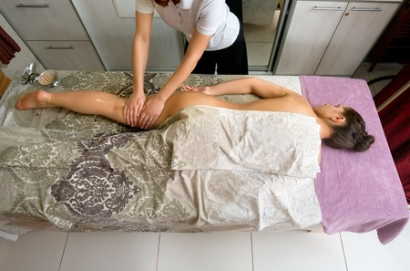 beauty body: Top view of beautiful woman lying on massage table, therapist massaging her body. Young girl getting spa treatment. Beauty and helth care concept