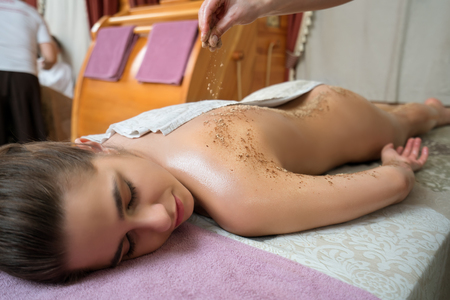 girls naked: Spa massage. Image of young girl lying on her stomach