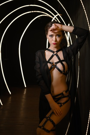 Sexy brunnette in black shiffon gown and thin belts all over her body posing topless