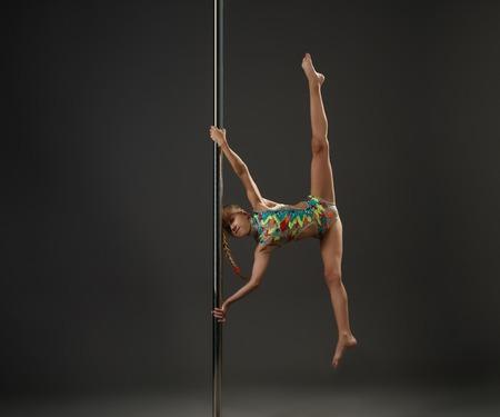 acrobacia: niña de adolescentes en la toma de traje de baño abigarrada ejerce sobre el pilón en el estudio