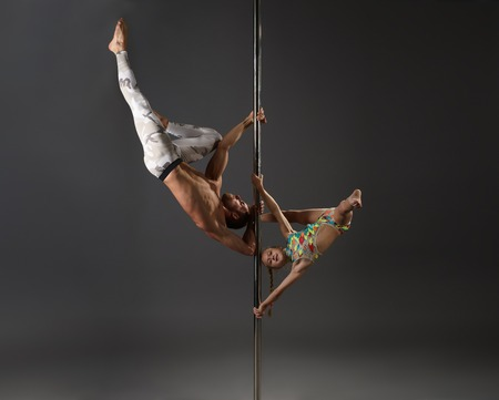 Athletic young male pole dancer making exercises in pair with girl in studio