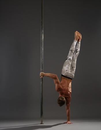 Athletic young pole dancer in leggings standing on one hand by pylon in studio