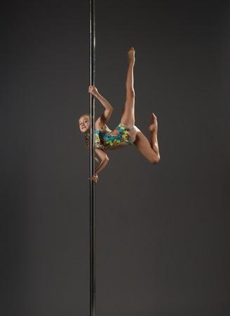Shot of nice little girl in motley sports swimsuit exercising on pylon in studio Stock Photo