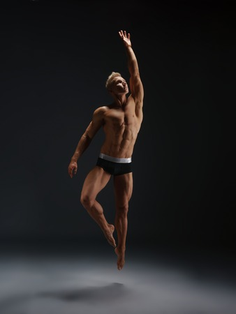 boy gymnast: Young male gymnast in shorts jumping and straightening his body gracefully with his hand up Stock Photo