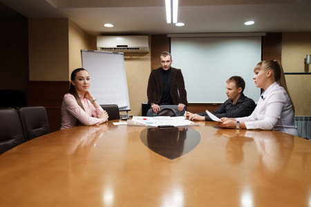 group strategy: Group of business people in formal wear sitting at meeting room and discussing marketing strategy  at office