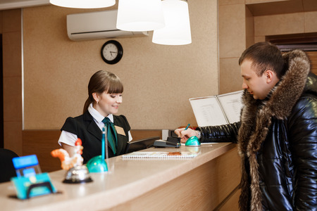 standing reception: Side view of female receptionist and male guest standing at hotel reception and  paying with check during check-in