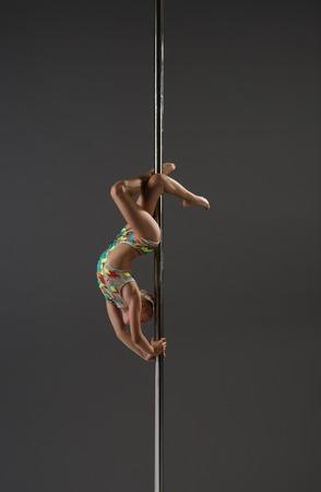 baile de la niña flexible en el estudio de danza de Polo. Mujer deportiva acróbata secundaria realizar en el pilón, fondo gris