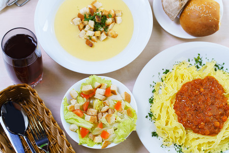 lunch meal: Business lunch concept. Top view image of  table with food. Meal consists of three dishes: Caesar salad, cream soup and pasta bolognese Stock Photo