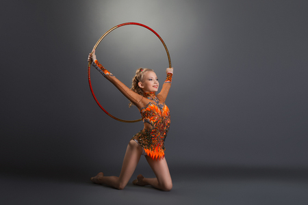 Young gymnast girl in bright leotard performing with hoop on grey studio background Stockfoto