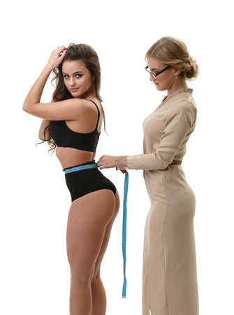 Professional female tailor  or clothes designer measuring waist of young athletic woman with perfect body, isolated on white