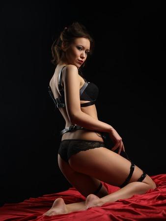sexy nackte frau: Rückansicht der dominante Herrin in schwarzen Dessous und Ledergürtel zur Kamera posiert auf dunklem Hintergrund. Modell trägt erotische Unterwäsche, Studioaufnahme